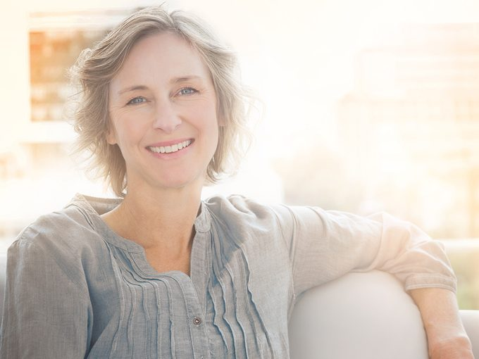 Anxiety attack, calm, smiling mature woman relaxes on her couch