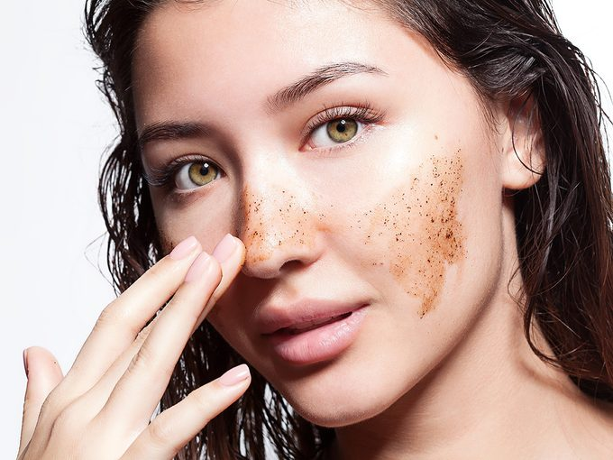 Exfoliation, woman scrubbing face