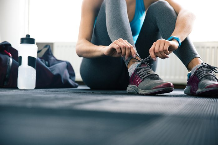 maximize your workout_woman tying shoes