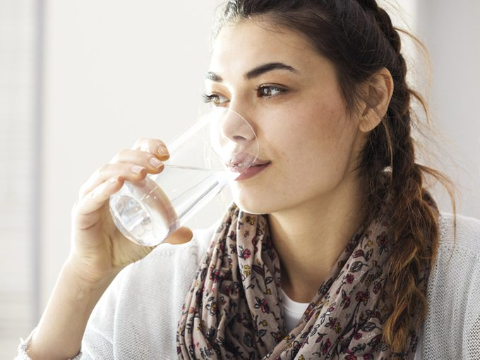 Chronic dry mouth, woman drinking glass of water