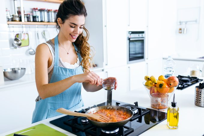 woman cooking spicy food - health benefits of spicy food