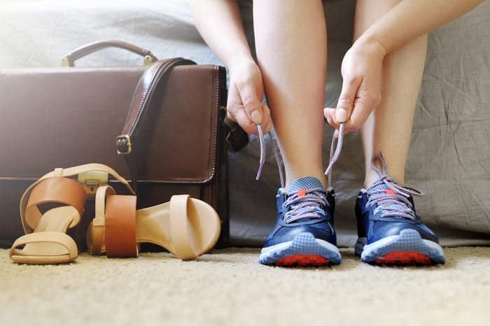 woman putting on sneakers