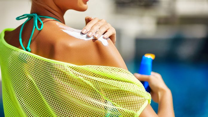 woman applying sunscreen for better breasts health