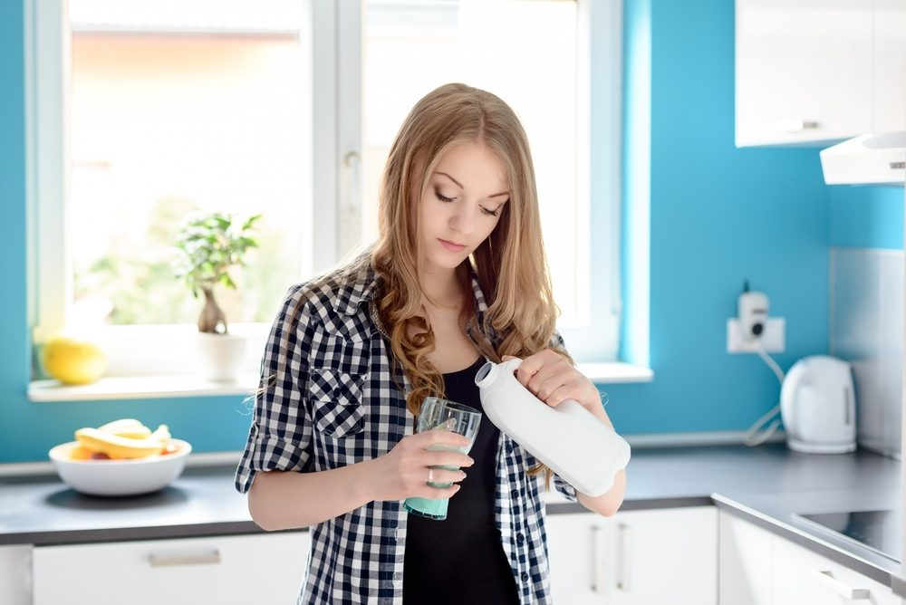 Lactose intolerant woman pours herself a glass of milk