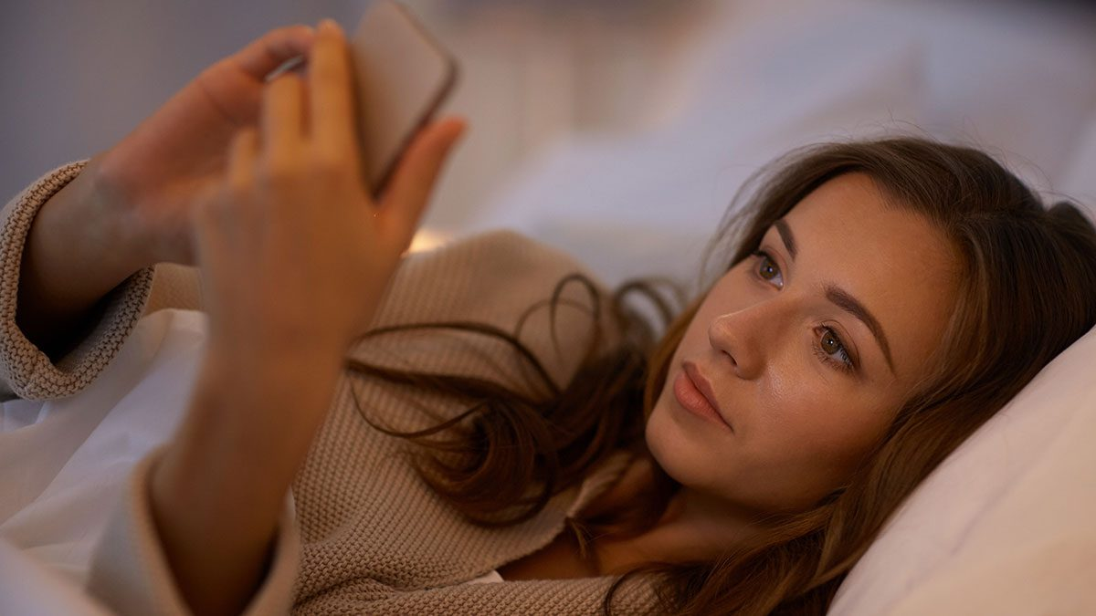Texting, woman on smartphone in bed