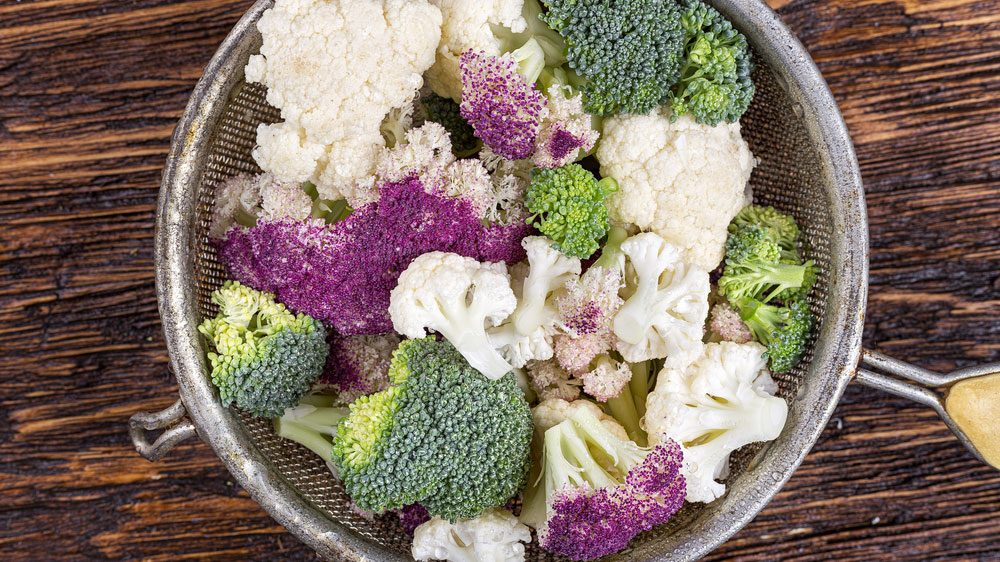 antiaging foods vegetabiles, a sieve filled with broccoli and cauliflower chunks