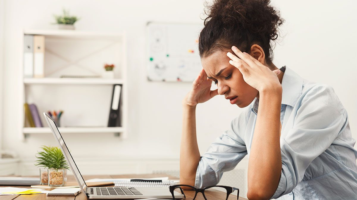 When to call in sick, woman at work desk