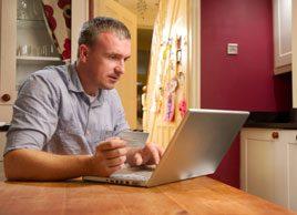 man shopping online computer debt