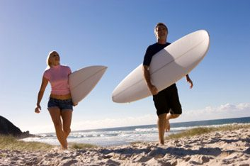 man and woman surfing