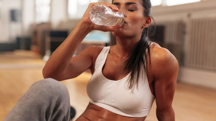 woman drinking water after a hard workout
