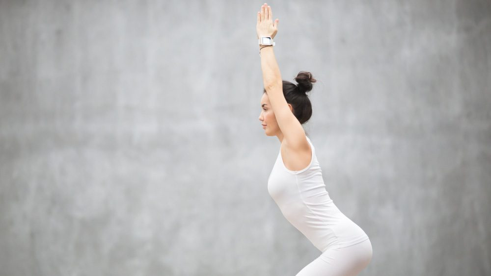 Woman with her hair up in a bun doing yoga