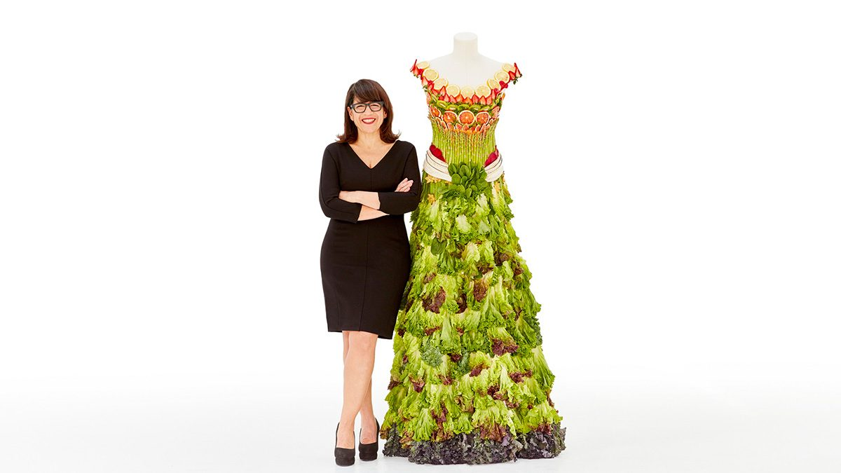 Designer Izzy Camilleri standing with a dress made out of greens