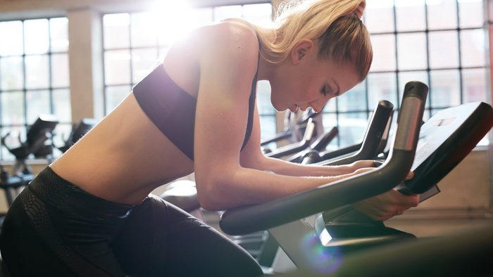 Spinning mistakes posture: woman hunched over the handles of her spin bike