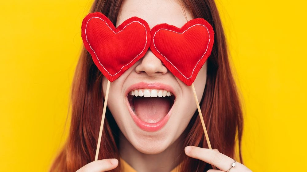 dark circles puffy eyes, woman covering her eyes with heart-shaped pillows