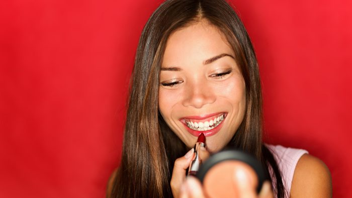 smiling woman putting on red lipstick