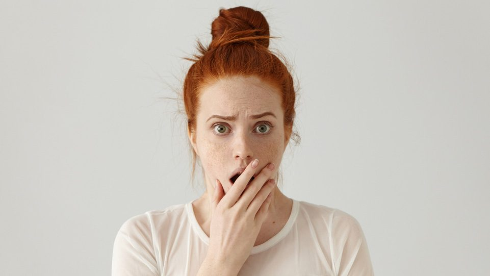 A red-headed woman holds her mouth in shock