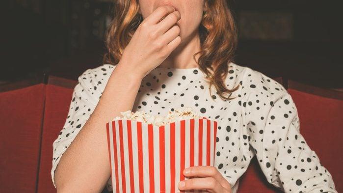 woman eating popcorn at the movies