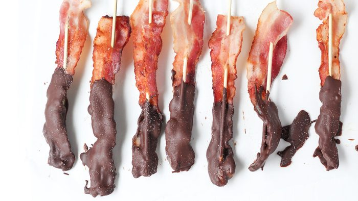 Skewers of bacon half dipped in chocolate, sitting on a white table, with chocolate spills