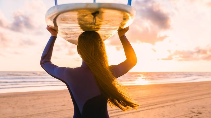 women at risk for injuries, woman on a beach about to go surfing