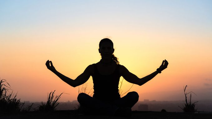 common autoimmune diseases in Canada, a woman doing the yoga lotus pose at sunset