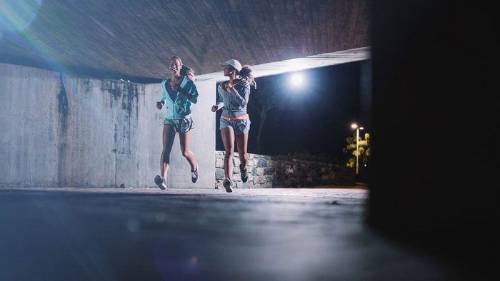 eat before a late night run, two women running under a bridge at night
