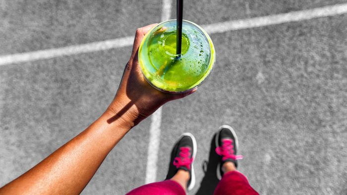 """What to eat before a run, a woman doing a """"from where I stand"""" selfie showing running shoes and a green smoothie"""
