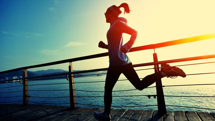 what to eat before an early morning run, a woman running along the dock during sunrise