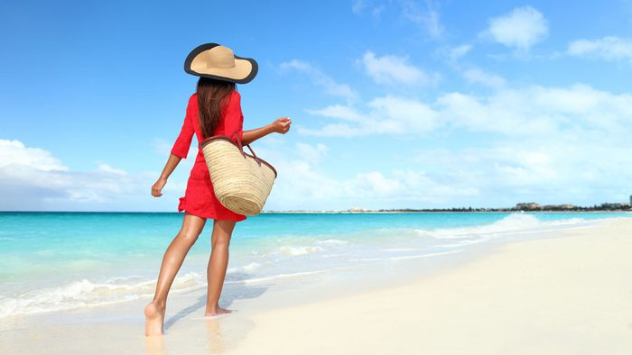 summer layering, a woman walks along the beach with a sun hat, a coverup dress and an oversized tote