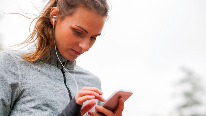 Canadian Workout Playlist, woman setting her songs on her phone before a run