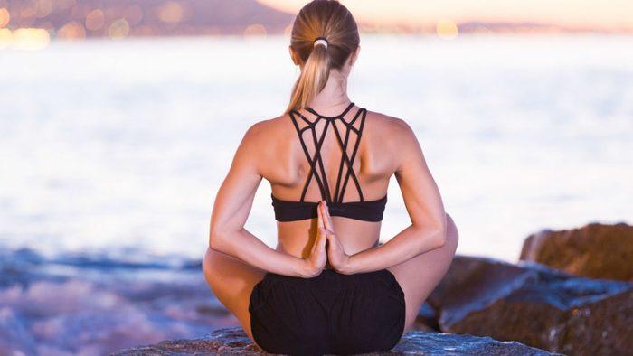 wellness getaways breathe meditation, a woman meditating on the beach