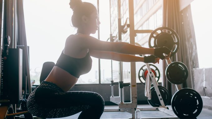 age metabolism slows, woman doing a squat in the gym