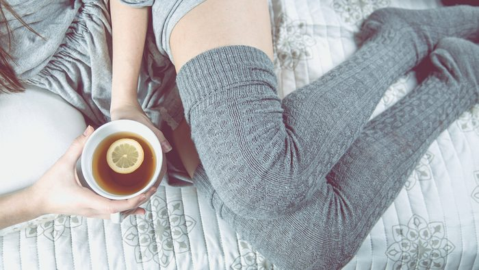 diet tips for sleeping, woman in bed with a cup of tea