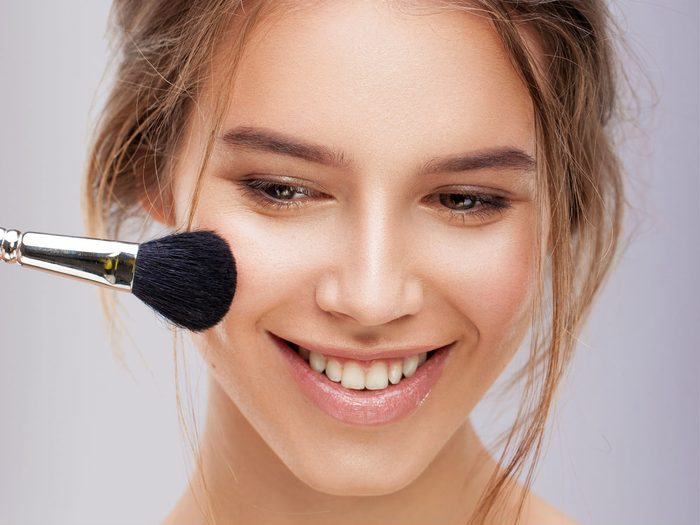 dull skin makeup mistakes, wrong colour foundation, woman applying makeup