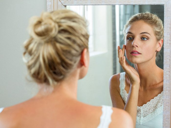 Turmeric Benefits for Skin, woman looking in the mirror
