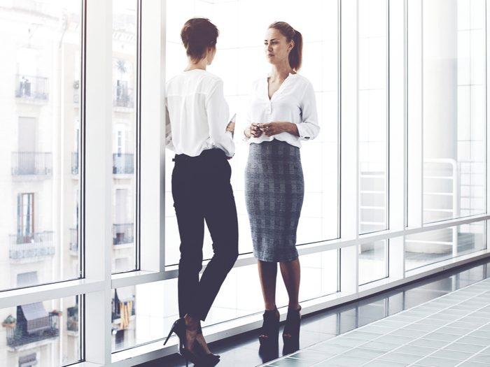 walk more stand at work, two women in an office building talking in the hallway