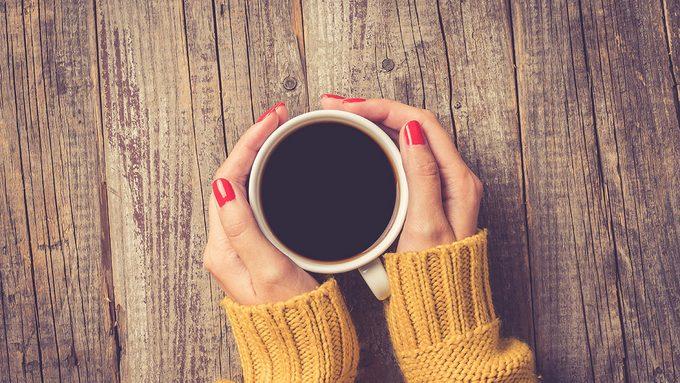 Coffee, woman holding her mug of coffee