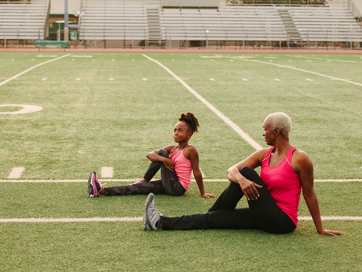 Older woman stretches on field with granddaughter
