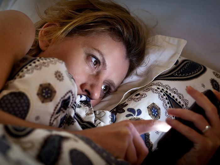 Aging, Woman checking phone from bed