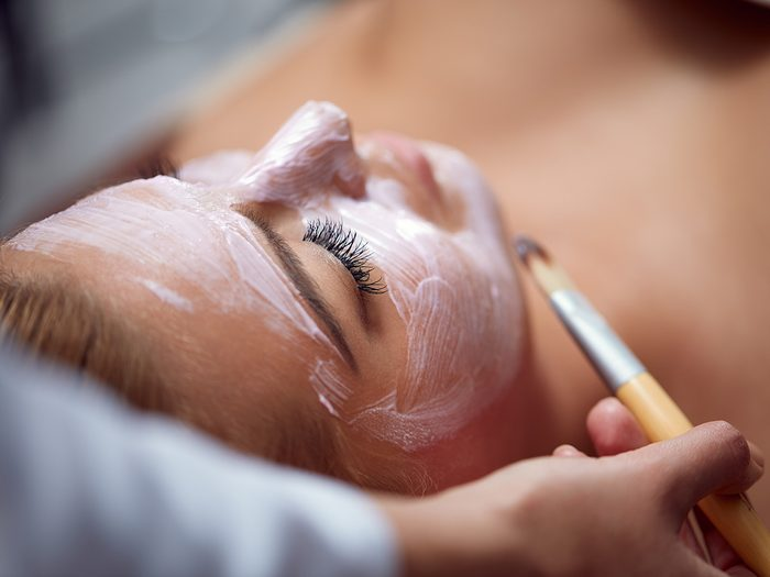 Blackheads, woman lying down for professional facial and having treatment painted on her face