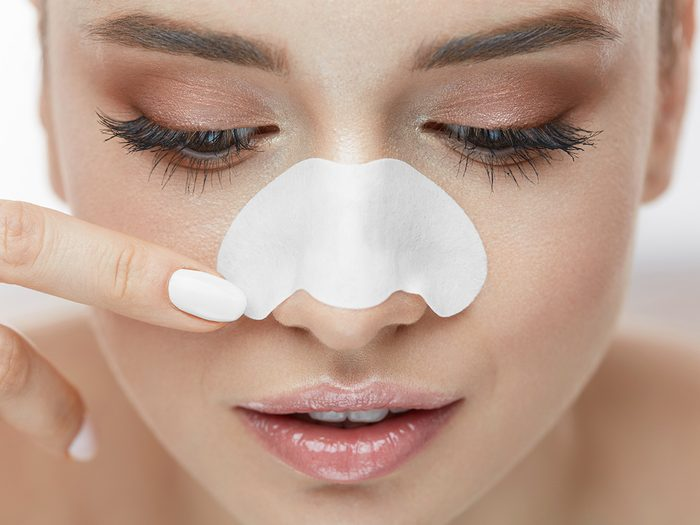 Blackheads, woman about to remove a pore strip from her nose
