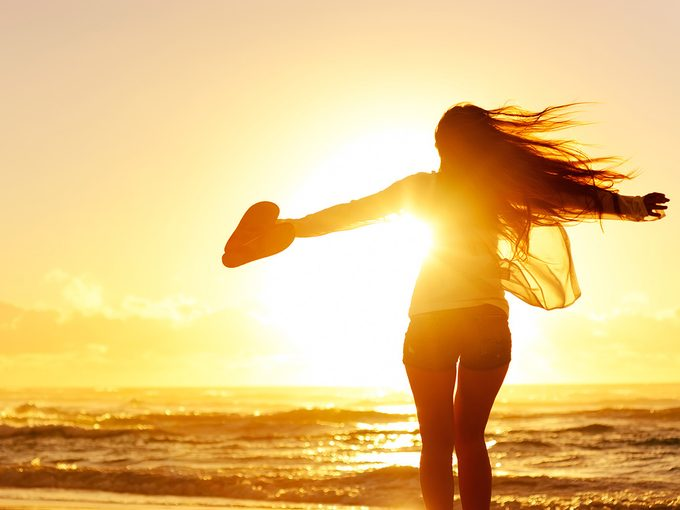 Body image, Woman standing on a beach, silhouetted in front of a sunset, with her arms flung wide
