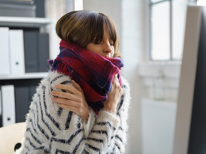 Cold weather, Woman shivers at her desk. She is bundled in a scarf and sweater and clutches her shoulders.
