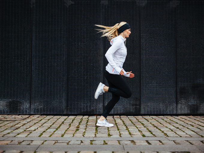 Cold weather, woman runs through urban city street. She wears full running gear. Weather looks grey and cold.