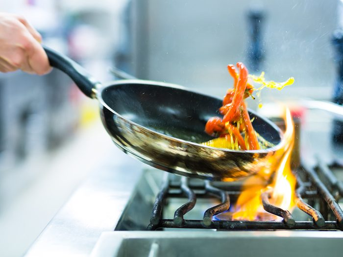 Cooking mistakes, chef sauteeing food over stove