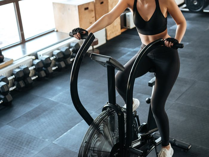 Flat stomach, woman in gym working out on stationary bike