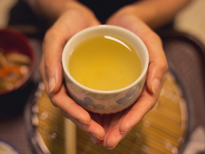 Green tea, Young woman cupping a cup of green tea with no handle. Shot just on her hands.