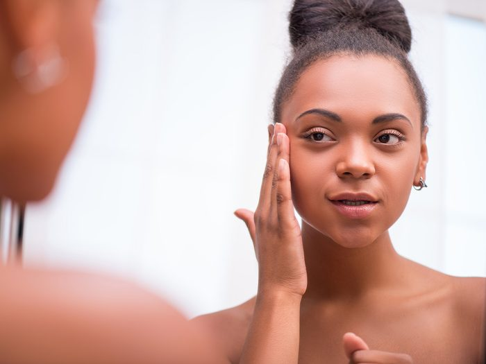 Green tea, young woman checks her skin for acne in a mirror
