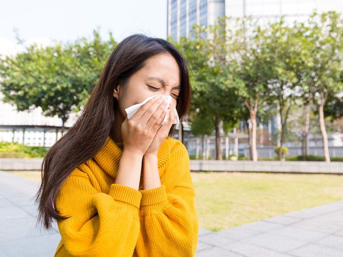 Green tea, Young woman sneezes into a tissue outdoors