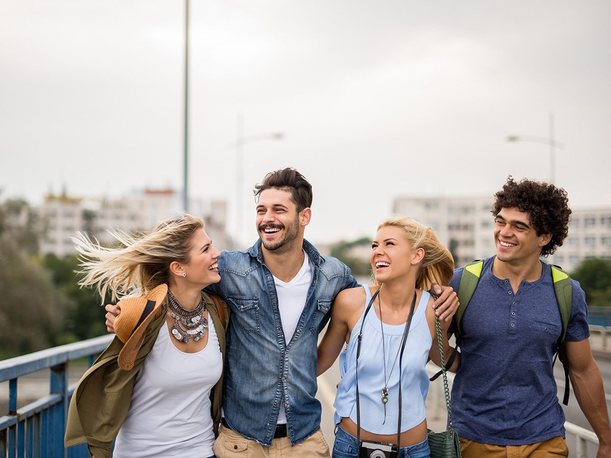 Happiness, group of happy friends walking arm in arm