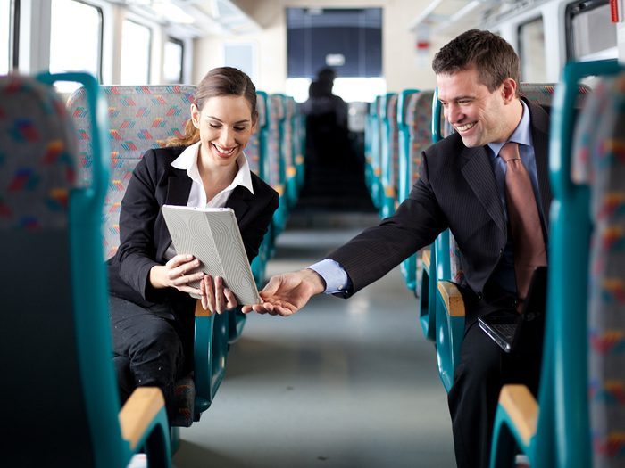 Happiness, man and woman chatting across aisle during train commute